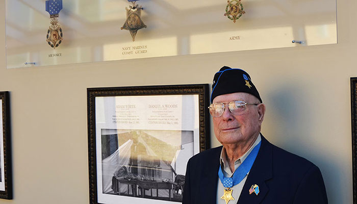 Woody in front of a Medal of Honor Wall of Memory